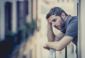 Young Man At Balcony In Depression Suffering Emotional Crisis